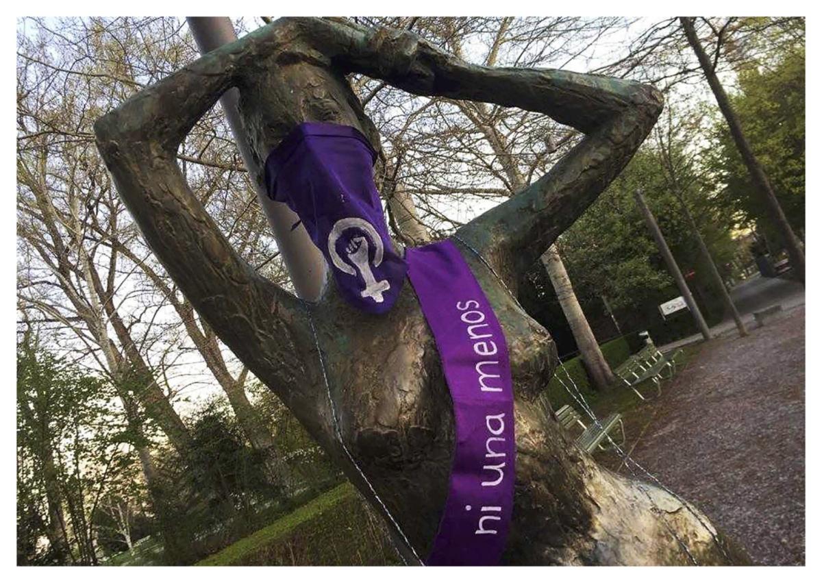 """Eine Statue einer nackten Frau in einem Park, sie wurde mit einem violetten Bandana mit einem Venussymbol vermumt und ihr wurde eine Schärpe umgelegt auf der steht """"Ni una menos"""""""