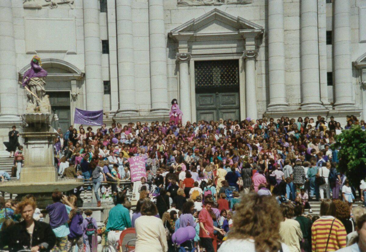 buntes Bild der Demonstration aus leicht erhöhter Perspektive, ganz viele FLINT und violette Ballone und Tücher und die Brunnestatue am linken Rand wurde violett eingekleidet