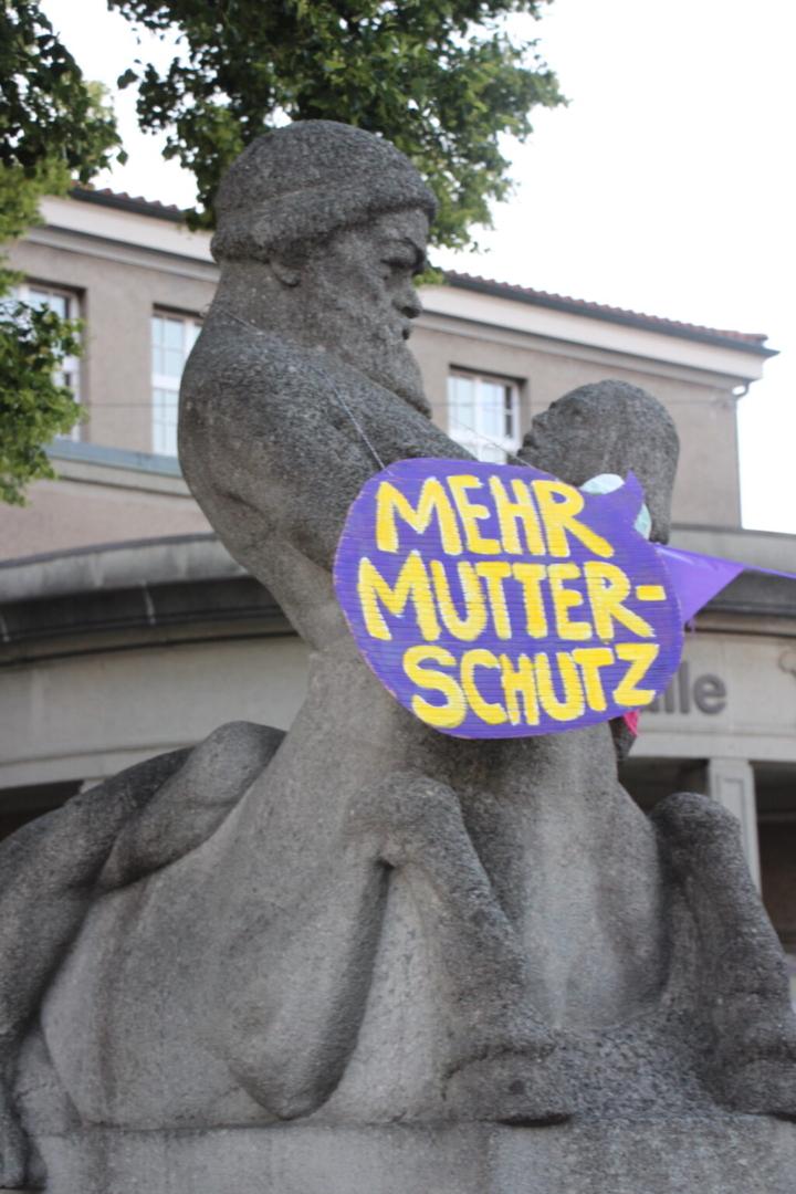 """EKdM Kartonschild """"Mehr Mutterschutz"""" an Statue."""