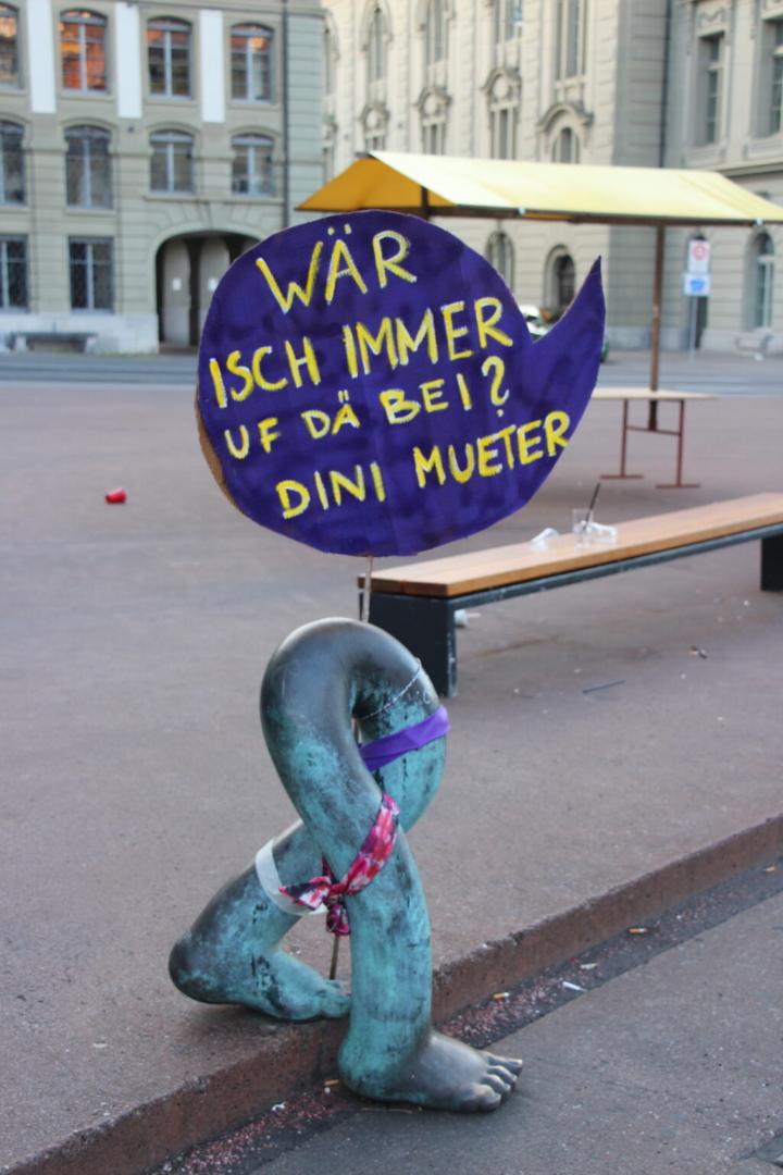 """EKdM Kartonschild """"Wär isch immer uf de Bei? Dini Mueter"""" an Denkmal."""
