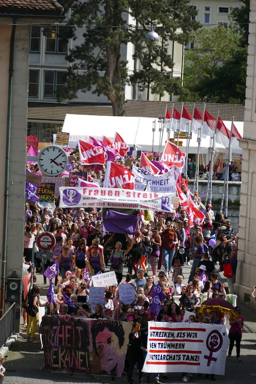 Foto des Demozugs am 14. Juni 2019 in Solothurn in einer Gasse mit ganz vielen Pancartas, Transparenten und Unia-Flaggen